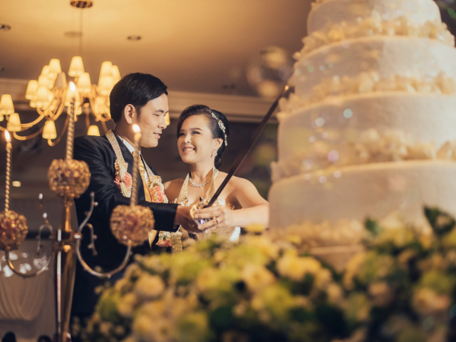 Bride and groom are cutting cake for celebration on their wedding day